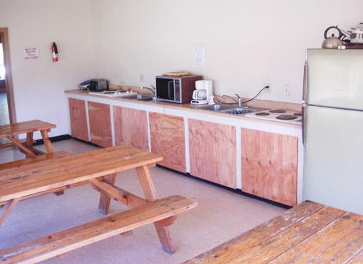 The bunkhouse has a kitchen for the guests. It contains a sink, microwave, ranges, coffee maker, toaster, several refrigerators, and tables.